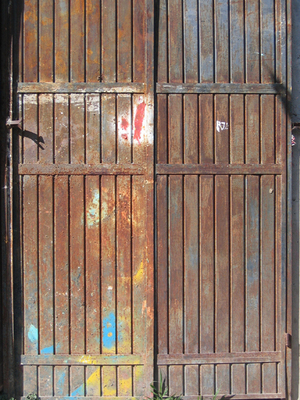 A steel door with splashes of orange and blue