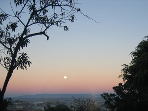 A full moon sets in the west amid the reflected glow of the sunrise.